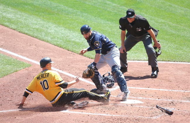 Apr 17, 2016; Pittsburgh, PA, USA; Milwaukee Brewers catcher Jonathan Lucroy (20) steps on home plate to force out Pittsburgh Pirates shortstop Jordy Mercer (10) during the third inning at PNC Park. Mandatory Credit: Charles LeClaire-USA TODAY Sports